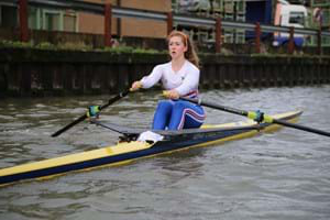 student rowing in a river