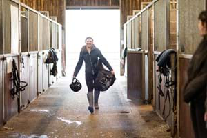 Student walking down a barn aisle on Hartpury livery yard