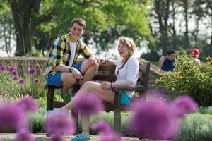 Two students sitting and laughing on a bench in a garden