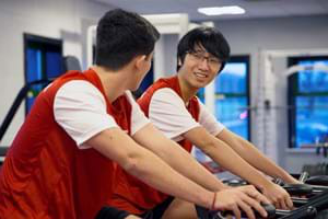 Two students using exercise bikes in the Hartpury gym