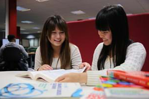 Two students studying together in the library