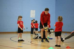 A Hartpury student teaching a group of younger children to pass a netball